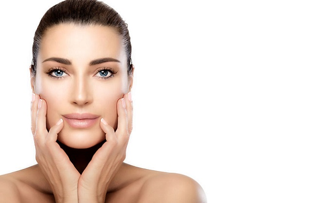 beauty model woman with hands on cheeks looking at camera with a serene expression in a beauty, skincare and spa concepts. perfect skin with no makeup makeup and manicured nails. portrait isolated on white