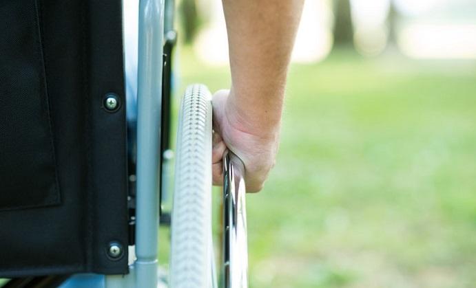 detail of a man using a wheelchair in a park